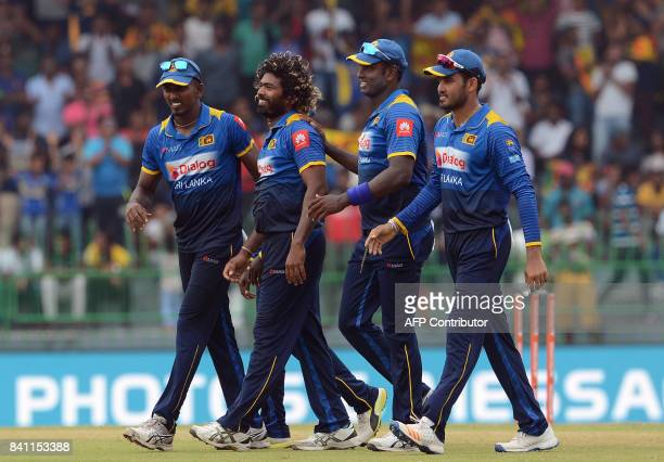 Sri Lankan cricketer Lasith Malinga celebrates with his teammates after he dismissed Indian cricket captain Virat Kohli during the fourth one day...