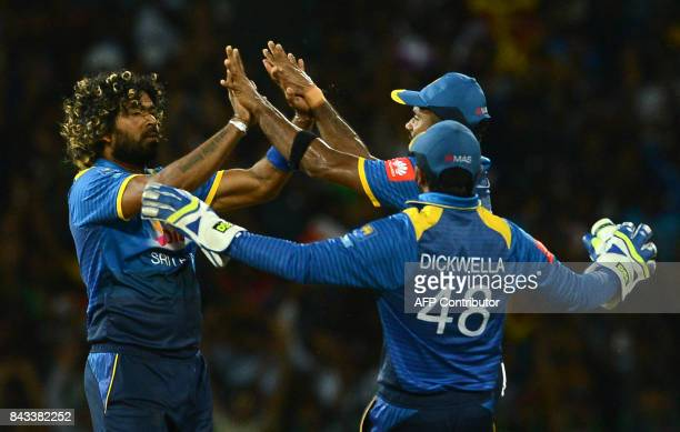 Sri Lankan cricketer Lasith Malinga celebrates with his teammates after he dismissed Indian cricketer Rohit Sharma during the Twenty20 international...