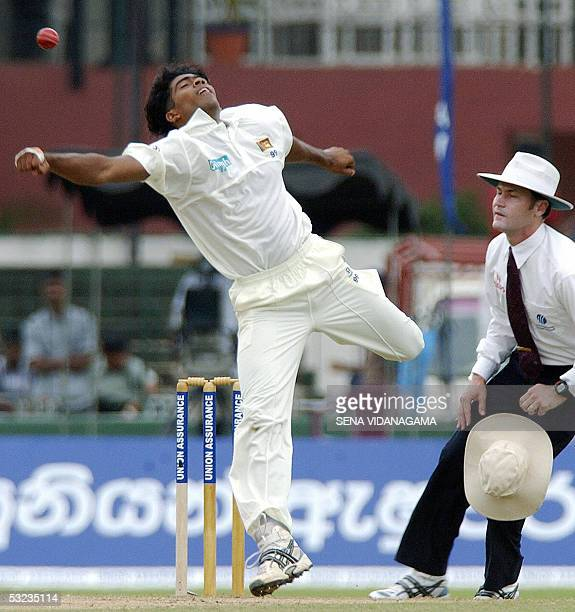 Sri Lankan cricketer Lasith Malinga is watched by umpire Simon Taufel as he attempst to hold onto a caught and bowled chance during the second day of...
