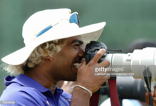 Sri Lankan cricketer Lasith Malinga looks through a camera during the third and final One Day International match between Sri Lanka and Bangladesh at...