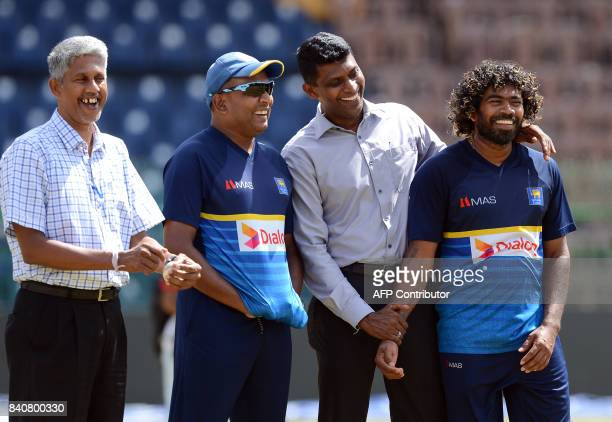 Sri Lankan cricketer Lasith Malinga shares a light moment with selection committee member Eric Upashantha Ranjit Madurusinghe and spinng bowling...