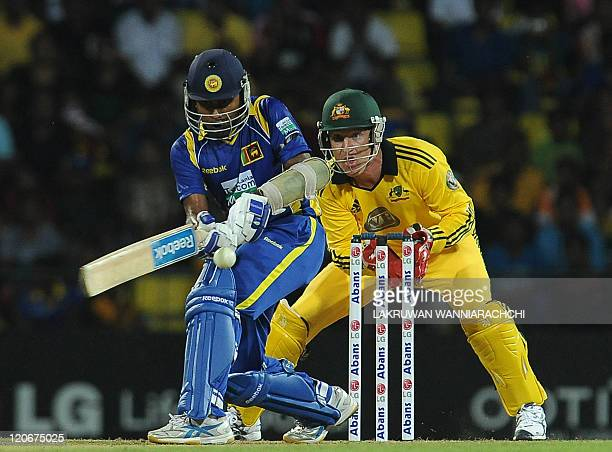 Sri Lankan cricketer Mahela Jayawardene is watched by Australian wicketkeeper Brad Haddin as he plays a shot during the second Twenty20 match between...