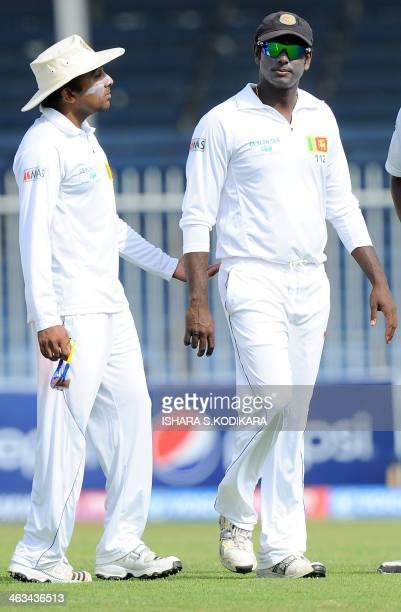 Sri Lankan cricketer Mahela Jayawardene speaks with team captain Angelo Mathews during the third day of the third and final cricket Test match...