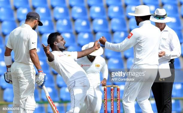 Sri Lankan cricketer Malinda Pushpakumara celebrates with his teammates after he dismissed Indian cricketer Ajinkya Rahane during the first day of...