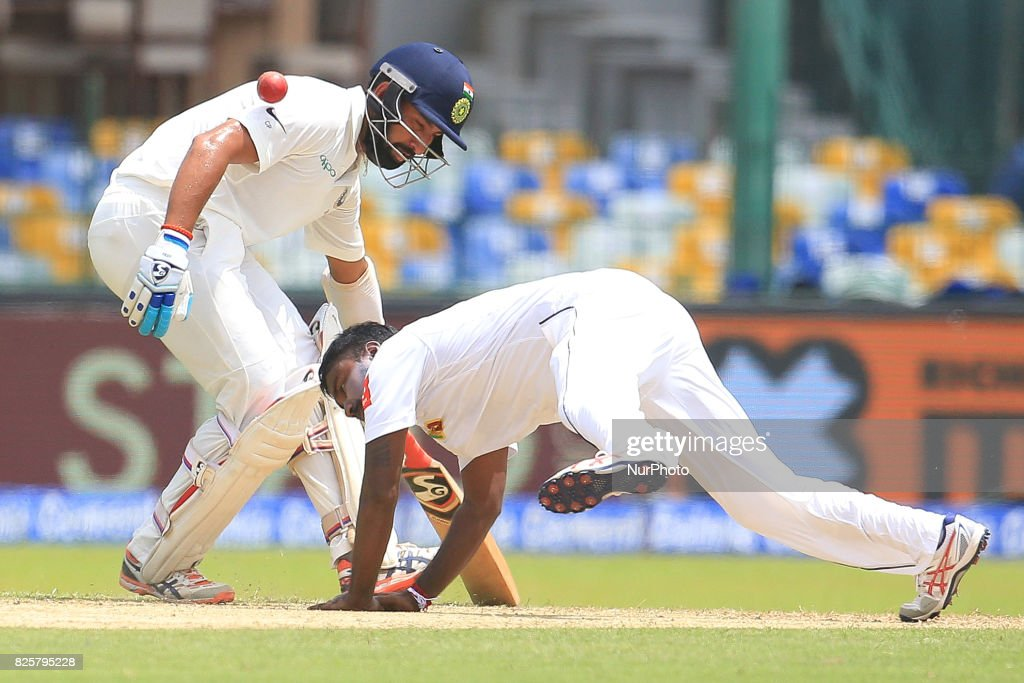 Sri Lankan cricketer Malinda Pushpakumara(R) tries to stop the ball as Indian cricketer Cheteshwar Pujara looks on during the 1st Day's play in the 2nd Test match between Sri Lanka and India at the SSC International cricket stadium at the capital city of Colombo, Sri Lanka on Thursday 03 August 2017.