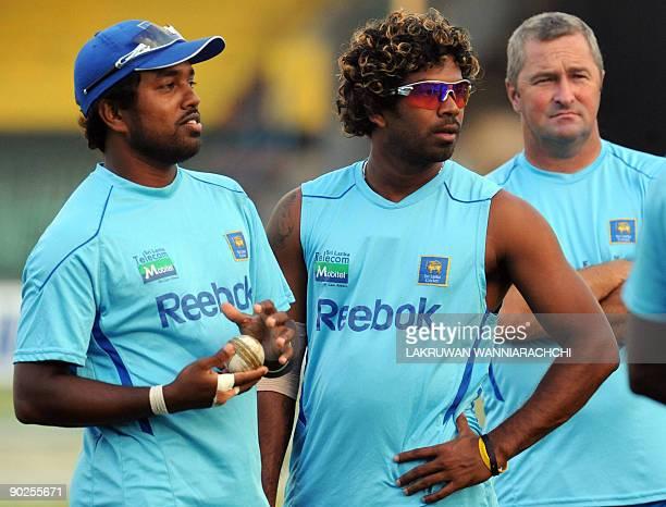 Sri Lankan cricketer Malinga Bandara and teammate Lasith Malinga look on during a practice session at tR Premadasa Stadium in Colombo on September 1,...