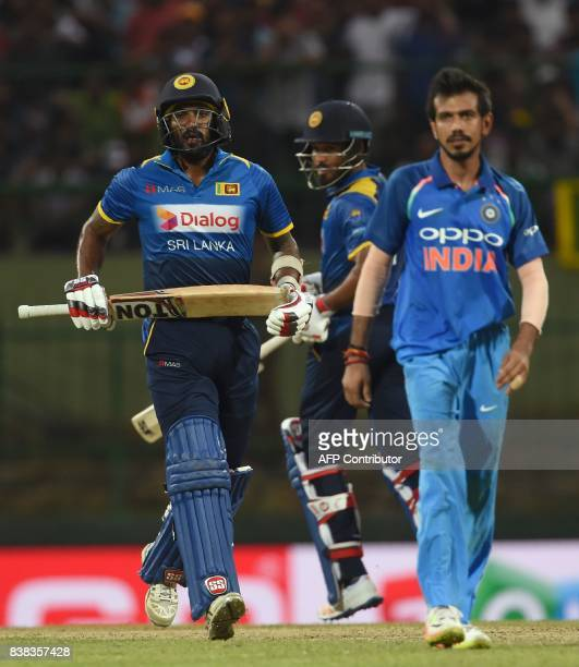 Sri Lankan cricketer Milinda Siriwardana and Chamara Kapugedera run between the wickets as Indian cricketer Yuzvendra Chahal looks on during the...