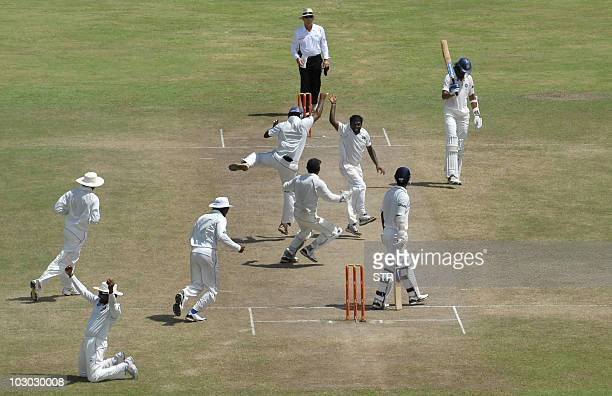 Sri Lankan cricketer Muttiah Muralitharan celebrates with teammates on claiming his 800th Test wicket with the dismissal of Indian cricketer Pragyan...