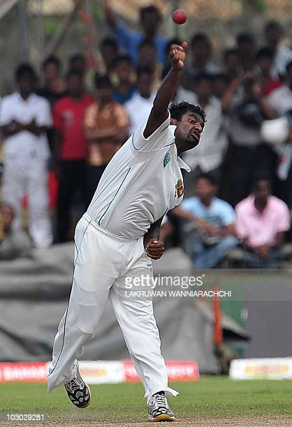 Sri Lankan cricketer Muttiah Muralitharan delivers a ball during the fifth day of the first Test match between Sri Lanka and India at The Galle...