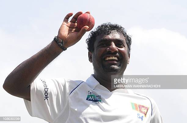 Sri Lankan cricketer Muttiah Muralitharan holds up the cricket ball as he walks back to the pavilion at the end of India's second innings during the...