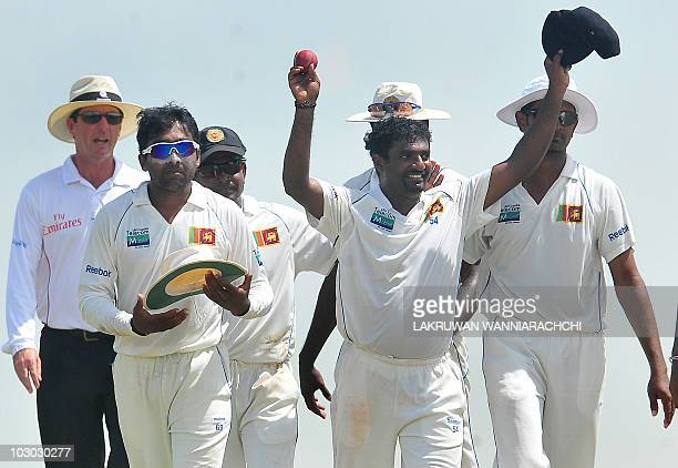 Sri Lankan cricketer Muttiah Muralitharan holds up the cricket ball as he walks back to the pavilion with teammates at the end of India's second...