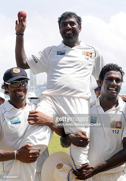 Sri Lankan cricketer Muttiah Muralitharan holds up the cricket ball as he is carried on the shoulders of his team mates Chanaka Welegedara and Angelo...