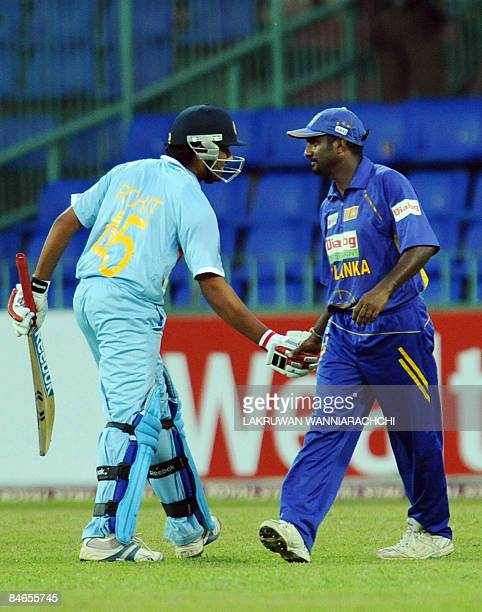 Sri Lankan cricketer Muttiah Muralitharan is congratulated by Indian cricketer Rohit Sharma after taking his 503rd One Day International wicket...