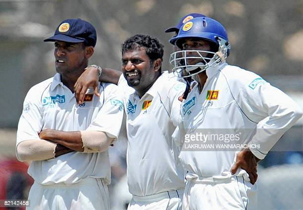 Sri Lankan cricketer Muttiah Muralitharan with teammates Thilan Samaraweera and Tillekeratne Dilshan wait for a decision from the third umpire for...