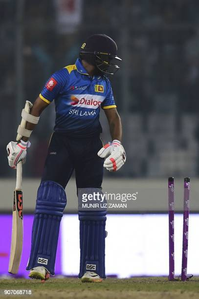 Sri Lankan cricketer Niroshan Dickwella reacts after being dismissed by Bangladesh cricketer Mustafizur Rahman during the third one day international...