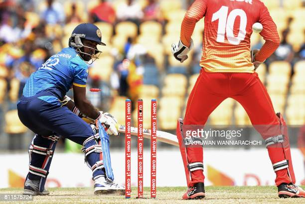 Sri Lankan cricketer Nuwan Kulasekara gets dismissed by Zimbabwe's cricket captain Graeme Creme as wicketkeeper Peter Moor looks on during the fifth...