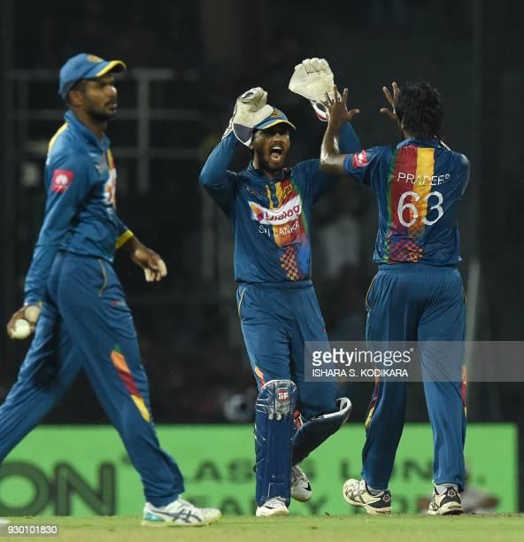 Sri Lankan cricketer Nuwan Pradeep and team captain Dinesh Chandimal celebrate after he dismissed Bangladesh cricketer Liton Das during the third...