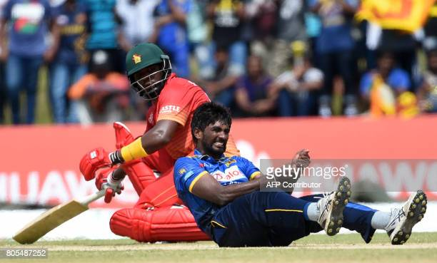 Sri Lankan cricketer Nuwan Pradeep reacts as Zimbabwe cricketer Hamilton Masakadza looks on during the second oneday internationals cricket match...