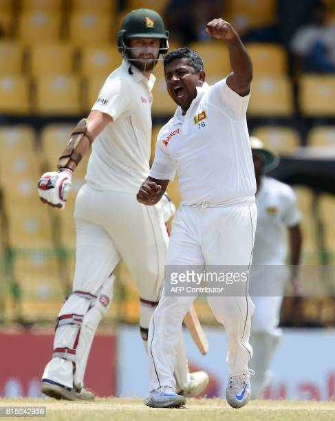 Sri Lankan cricketer Rangana Herath celebrates after he dismissed Zimbabwe's cricketer Hamilton Masakadza as cricketer Craig Ervine looks on during...