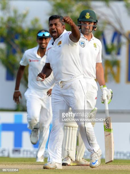 Sri Lankan cricketer Rangana Herath celebrates after he dismissed South Africa's Aiden Markram during the first day of the opening Test match between...