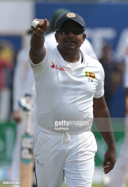 Sri Lankan cricketer Rangana Herath gestures to his dressing room during the 3rd day's play in the first Test cricket match between Sri Lanka and...