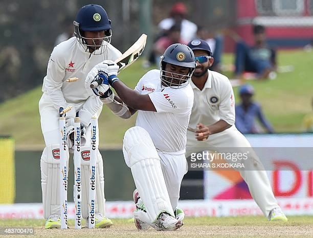 Sri Lankan cricketer Rangana Herath is dismissed by Indian bowler Ravichandran Ashwin as Indian wicketkeeper Wriddhiman Saha looks on during the...
