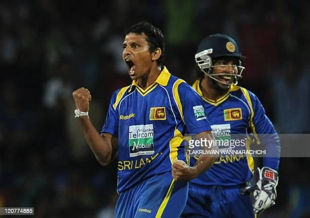 Sri Lankan cricketer Suraj Randiv celebrates with wicketkeeper Kumar Sangakkara after dismissing unseen Australian cricketer Shane Watson during the...