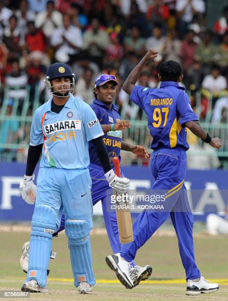 Sri Lankan cricketer Thilina Thushara Mirando and teammate Chamara Kapugedara celebrate after the dismissal of Indian batsman Virat Kohli during the...