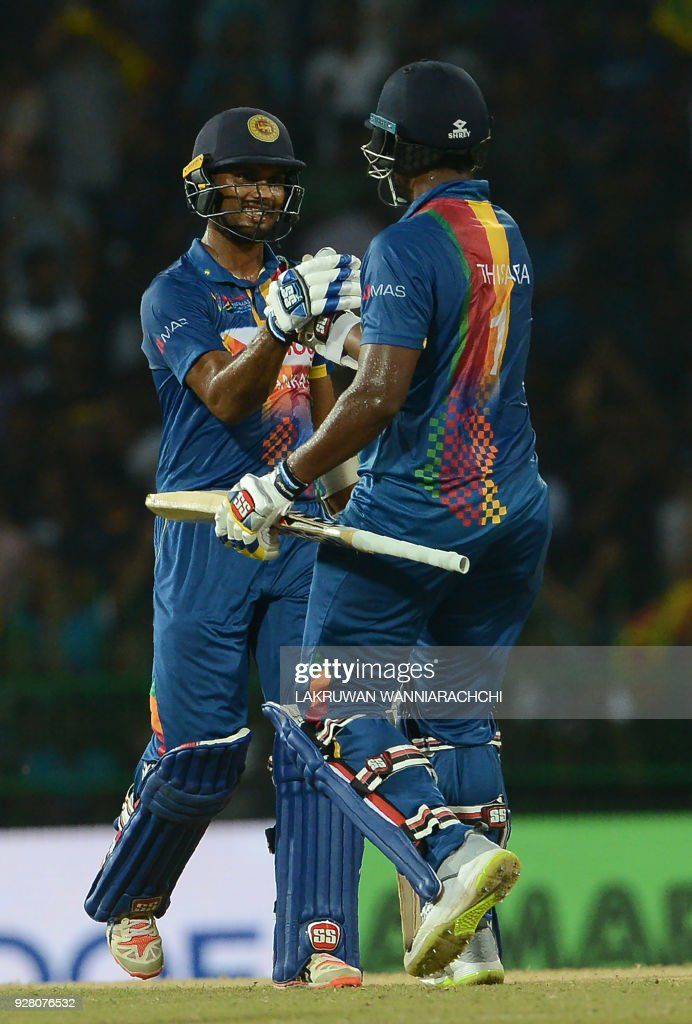Sri Lankan cricketer Thisara Perera (R) celebrates with teammate Dasun Shanaka after victory in the opening Twenty20 international cricket match between Sri Lanka and India for the Nidahas Trophy tri-nation Twenty20 tournament at The R. Premadasa Stadium in Colombo on March 6, 2018. The Nidahas Trophy tri-nation Twenty20 tournament involving Sri Lanka, Bangladesh and India. /