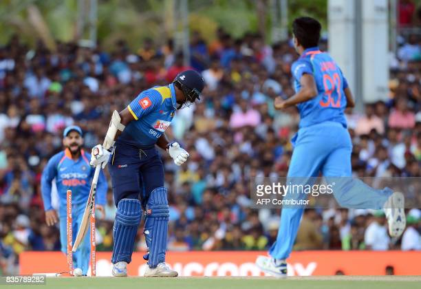 Sri Lankan cricketer Thisara Perera gets dismissed by Indian cricketer Jasprit Bumrah during the first One Day International cricket match between...