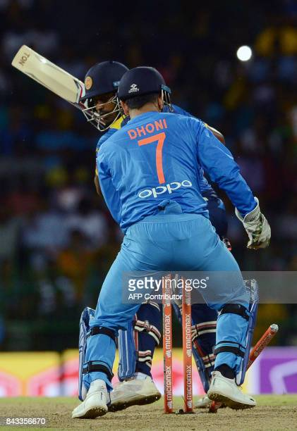 Sri Lankan cricketer Thisara Perera is dismissed by unseen Indian cricketer Yuzvendra Chahal as wicketkeeper Mahendra Singh Dhoni look on during the...