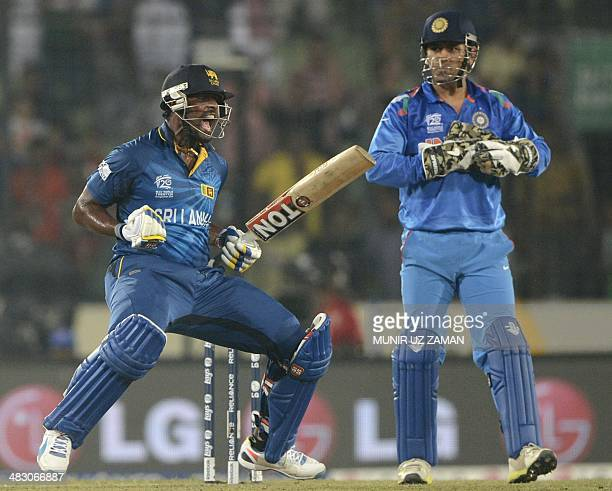 Sri Lankan cricketer Thisara Perera reacts following his team's win as India cricket captain Mahendra Singh Dhoni looks on during the ICC World...