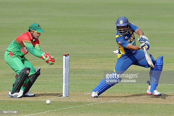 Sri Lankan cricketer Tillakaratne Dilshan plays a shot as Bangladesh cricket captain Mushfiqur Rahim looks on during the third and final one-day...