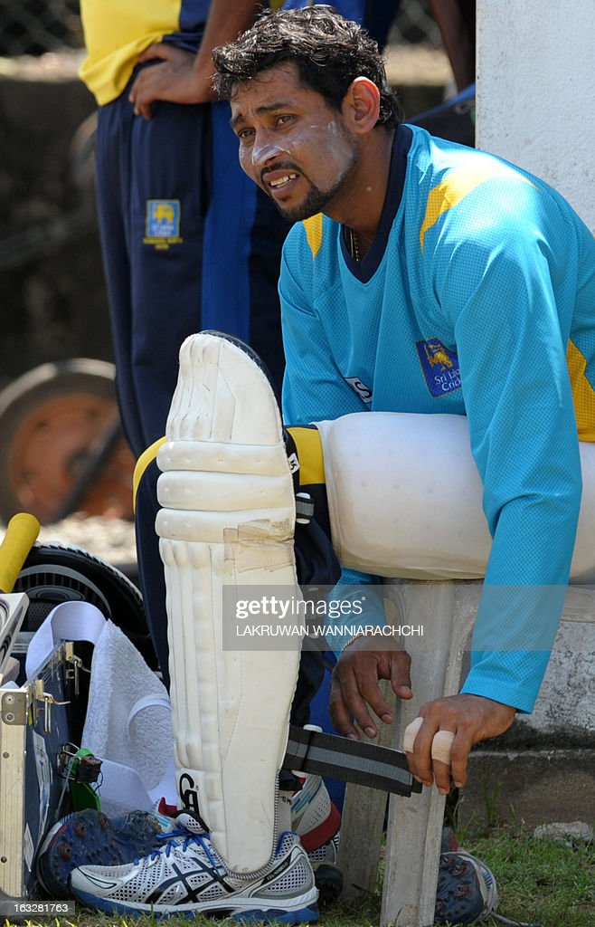 Sri Lankan cricketer Tillakaratne Dilshan puts on his leg pads for a practice session at the Galle International Cricket Stadium in Galle on March 7, 2013. Sri Lanka will play two Tests, three one-dayers and one Twenty20 cricket matches against Bangladesh, with the first Test to start March 8 in Galle.