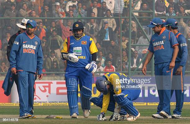 Sri Lankan cricketer Tillekaratne Dilshan is watched by teammate Sanath Jayasuriya and Indian fielders as he recovers after being hit by a ball...