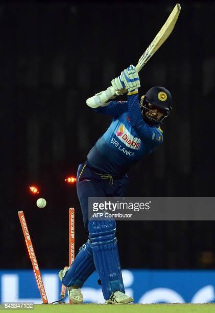 Sri Lankan cricketer Upul Tharanga is dismissed by Indian cricketer Bhuvneshwar Kumar during the Twenty20 international cricket match between Sri...