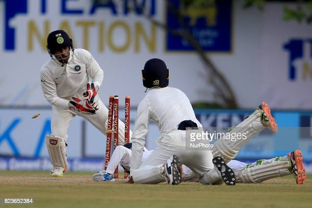 Sri Lankan cricketer Upul Tharanga is run out despite his dive as Indian Wicket keeper Wriddhiman Saha removes the bails during the 2nd Day's play in...