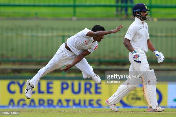 Sri Lankan cricketer Vishwa Fernando delivers a ball as India's Shikhar Dhawan looks on during the 1st Day's play in the 3rd Test match between Sri...