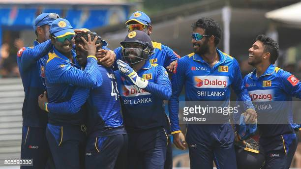 Sri Lankan cricketer wanidu hasaranga is hugged by Sri lankan team members after he completed taking a a hattrick of wickets against Zimbabwe during...