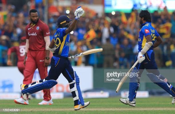 Sri Lankan cricketer Wanindu Hasaranga celebrates after scoring the winning runs as West Indies cricket captain Kieron Pollard reacts during the 1st...