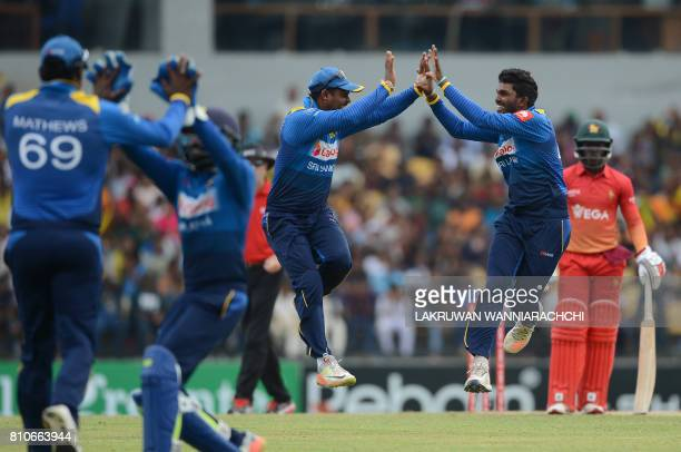 Sri Lankan cricketer Wanindu Hasaranga celebrates with his teammates after he dismissed Zimbabwe's cricketer Solomon Mire during the fourth oneday...