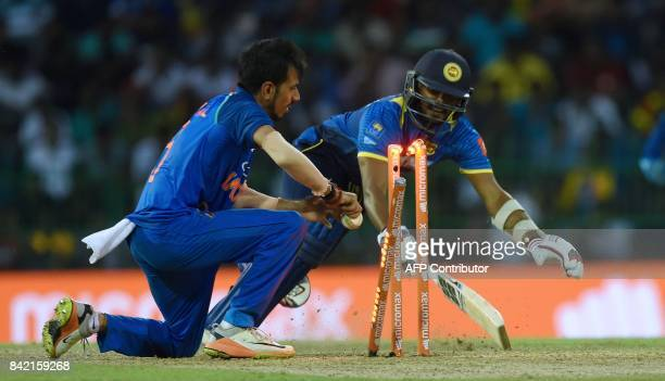Sri Lankan cricketer Wanindu Hasaranga is run out by Indian cricketer Yuzvendra Chahal during the final one day international cricket match between...