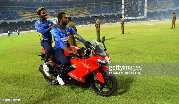 Sri Lankan cricketers Angelo Mathews sits with Akila Dananjaya on the prize Motor Bike after their team's won in the third One day International...