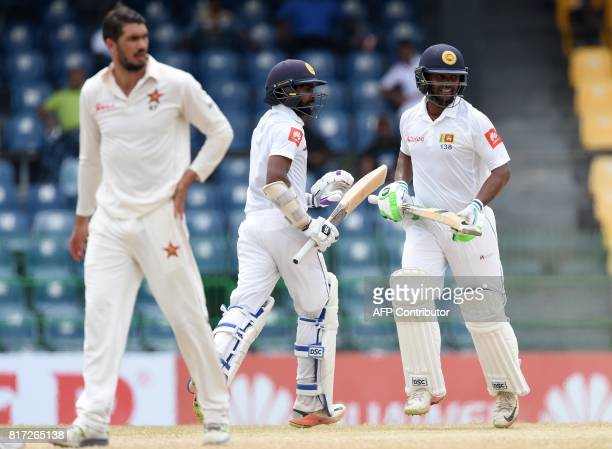 Sri Lankan cricketers Asela Gunaratne and Niroshan Dickwella run between the wickets as Zimbabwe cricket captain Graeme Cremer looks on during the...
