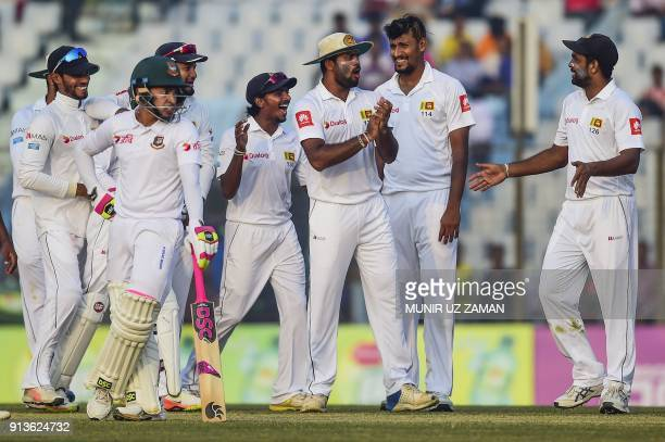 Sri Lankan cricketers celebrate after the dismissal of Bangladeshi cricketer Mushfiqur Rahim during the fourth day of the first cricket Test between...