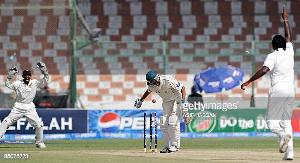 Sri Lankan cricketers Dilhara Fernando and Prasanna Jayawardene celebrate the dismissal of Pakistani cricketer Younus Khan during the fifth and final...
