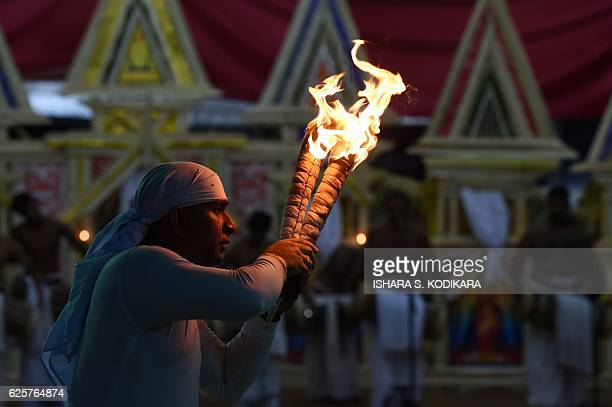 A Sri Lankan dancer performs during the traditional ritual 'Gammaduwa' ceremony in Colombo on November 25 2016 'Gammaduwa' shanthikarmais a ritual...