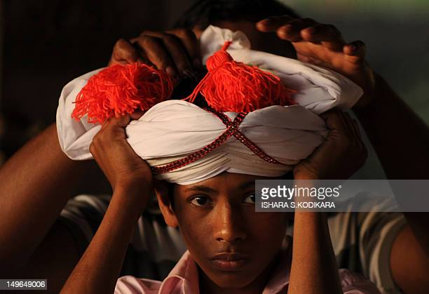 Sri Lankan dancer prepares to perform on the opening night of the annual Kandy Esala Perahera Festival in Kandy, some 116 kms from Colombo on August...