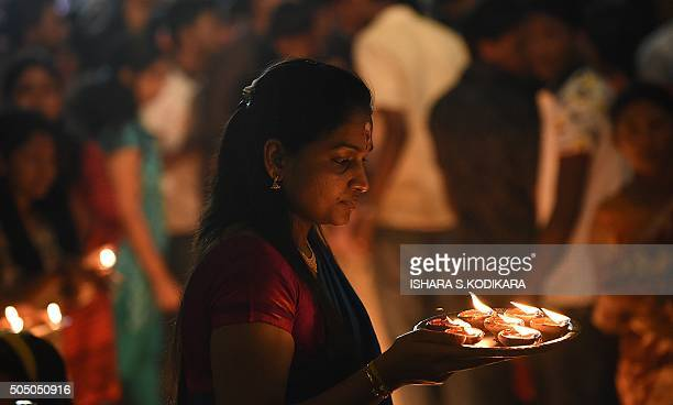 A Sri Lankan devotee holds oil lamps while offering prayers at a Hindu temple in Colombo on January 15 2016 Hindus in Sri Lanka are celebrating the...