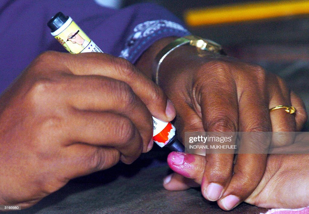 A Sri Lankan election official (L) marks : News Photo